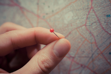 Foto de Close up on a hand placing a pin on a map - Imagen libre de derechos
