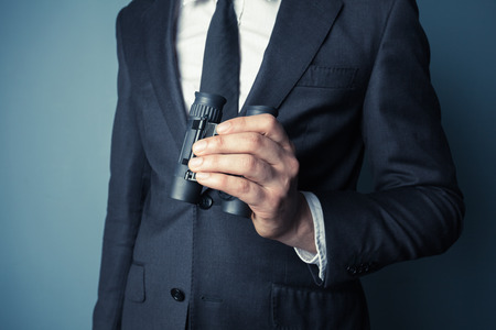 Businessman is holding binoculars