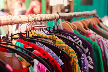 Clotes hanging on a rail at a street market outdoors