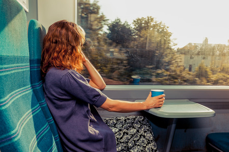 A young woman is sitting on a train with a cup of coffee and is looking out