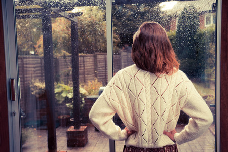 Photo pour A young woman is standing by the french doors in her house and is looking out at the rain - image libre de droit