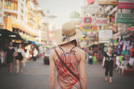 Foto de Rear view of a young woman walking the famous backpacker street Khao San in Bangkok, Thailand - Imagen libre de derechos