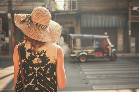 Foto de A young woman wearing a hat is walking in the streets of an asian country - Imagen libre de derechos