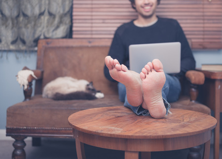 A happy barefoot man is resting his feet on a coffee table at home while working on his laptop, there is a cat sleeping next to him