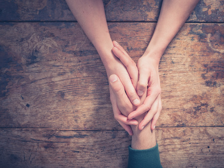 Photo pour Close up on a man and a woman holding hands at a wooden table - image libre de droit