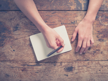 Photo for Close up on the hands of a young woman as she is writing in a small notepad at a wooden table - Royalty Free Image
