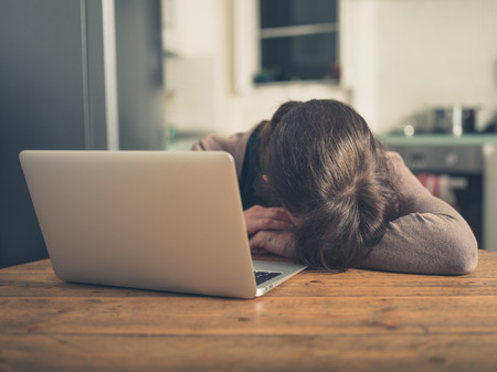 Photo pour A sad young woman is sleeping by her laptop in her kitchen at home - image libre de droit
