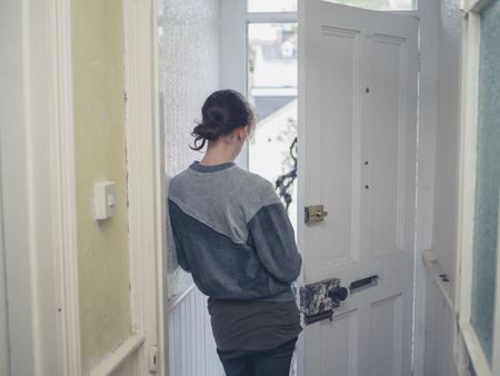 A young woman is standing in a doorway at home