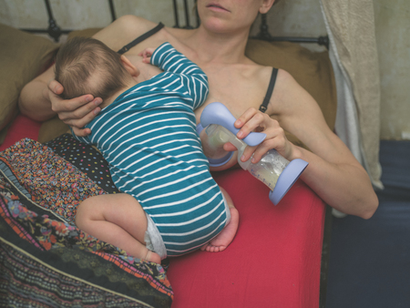 Photo for A young mother in bed is breastfeding her baby whilst expressing milk with a pump - Royalty Free Image