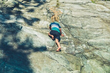 Photo pour A little toddler is climbing on some rocks in the summer - image libre de droit
