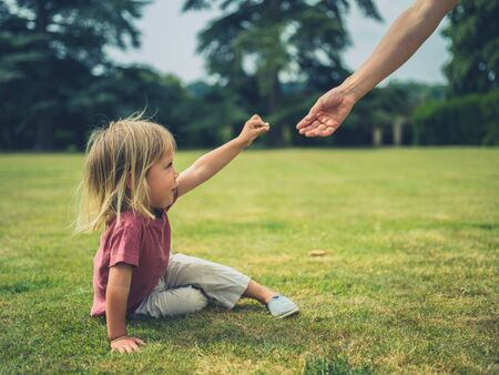 Photo for A little toddler is sitting on the grass in a park and is offering his mother a flower - Royalty Free Image