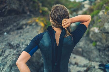 Photo pour A young woman on the beach is removing her wetsuit - image libre de droit