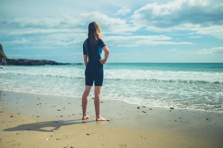 Photo pour A young woman wearing a wetsuit is standing on the beach in summer - image libre de droit