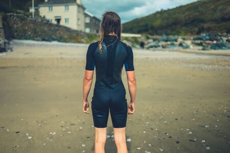 Photo pour A young woman wearing a wetsuit is standing on a beach in a village - image libre de droit