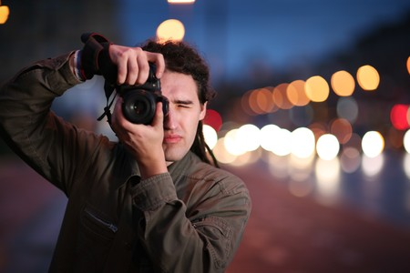 Photographer taking photo with DSLR camera at night. Shallow DOF.