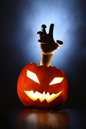 Foto de Hand of horror raising from glowing pupmkin lantern. - Imagen libre de derechos