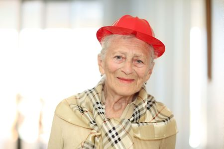 Portrait of a happy elderly woman in red hat. Shallow DOF.