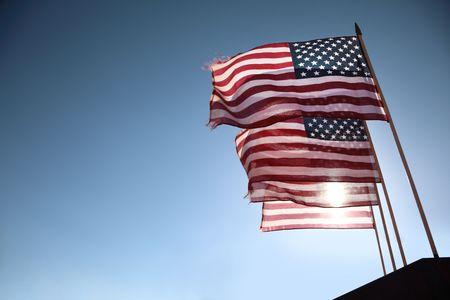 Photo pour Four American flags waving over blue sky - image libre de droit