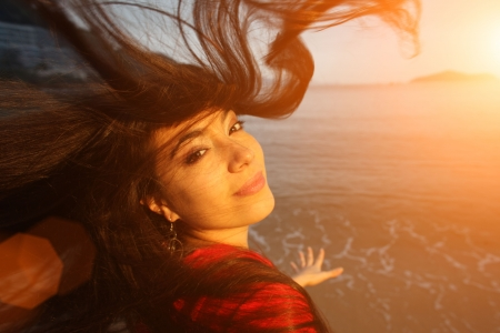 Photo pour Young beautiful woman with flying hair at beach at sunset looking at camera. - image libre de droit