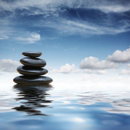 Stack of black zen pebble stones reflecting in water over blue sky background