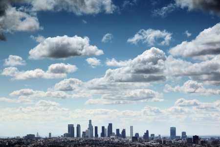 Downtown Los Angeles skyline under blue sky with scenic fluffy clouds.