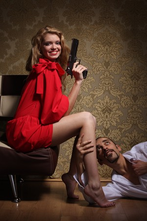 Sexy young adult woman with handgun sitting over man lying on floor and begging for mercy.