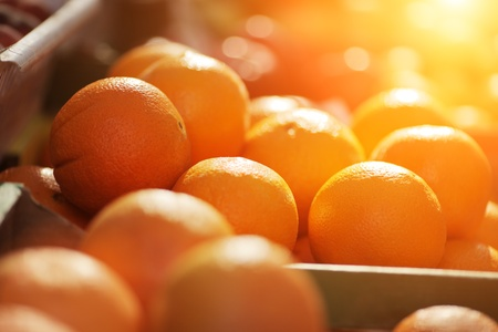 Fresh organic oranges on display on sunny day. Shallow DOF.