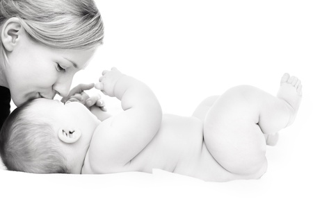 Photo pour Happy mother kissing baby girl against white background - image libre de droit