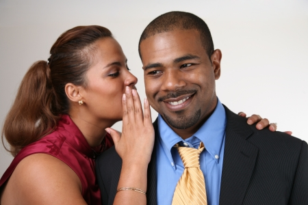 Woman whispering in husband's ear. Closeup, shallow DOF, focus on man.