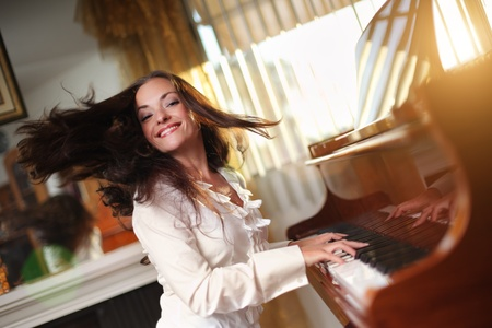 Photo pour Happy young woman playing piano indoors. Closeup, shallow DOF. - image libre de droit