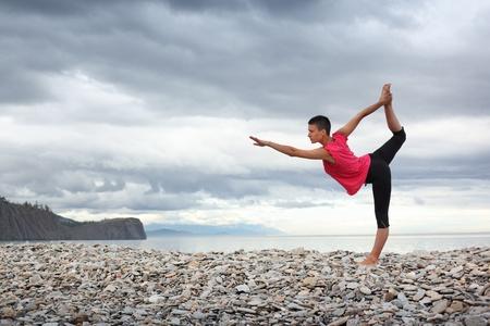Photo pour Young woman doing yoga stretch on stone beach at lake Baikal. - image libre de droit