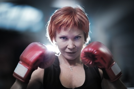 Portrait of mature woman in boxing gloves looking at camera. Closeup.