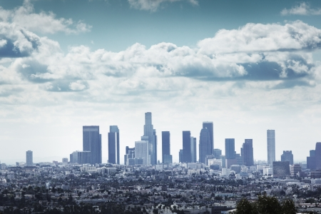 Downtown Los Angeles skyline over blue cloudy sky.