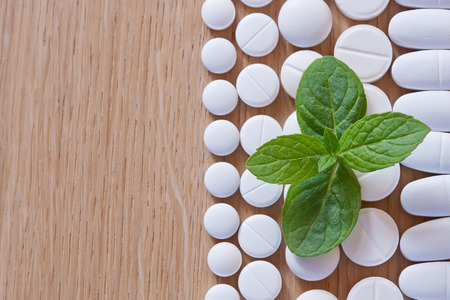White pills and foliage mint on a wooden background.