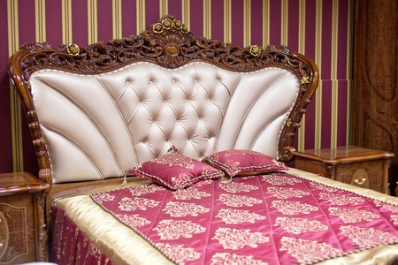 Double bed with decorative headboard.