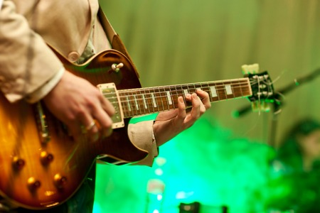 Photo for Musician plays on guitar in grey jacket. - Royalty Free Image