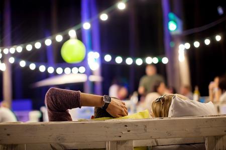 Foto de The young men in a summer cafe in the evening. - Imagen libre de derechos