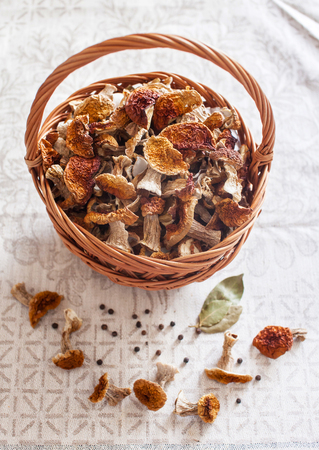 Dried white mushrooms in a beautiful wicker basket on the table.の写真素材
