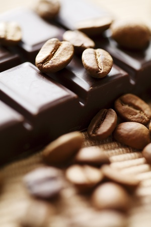 close up of dark chocolate with coffee beans around, shallow dof