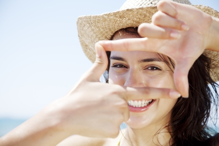 Photo pour young happy female looking through a frame made from her fingers - image libre de droit