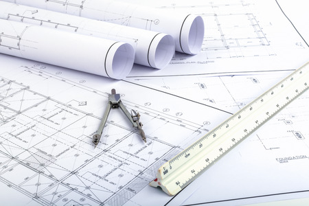 Photo pour Compasses and Architect scale ruler placed on the desk, filled with building plans. In order to work in a building - image libre de droit