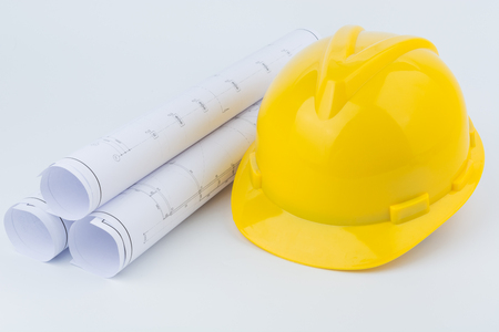 Yellow safety helmet and Scrolls of engineering drawings.