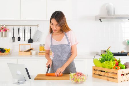 Foto de Asian beautiful woman, long hair, wearing a pink t-shirt and striped apron standing, slicing carrots on the table at modern white kitchen, and watching cooking video clip using tablet. - Imagen libre de derechos