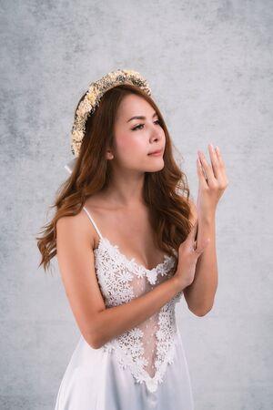 Photo pour Vintage style portrait beautiful woman wearing a white dress, flower crown on gray soft blurred background. - image libre de droit