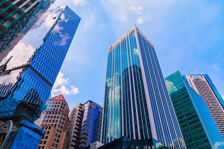 Photo pour Bottom view of High-rise building and modern skyscrapers in business district against blue sky. - image libre de droit