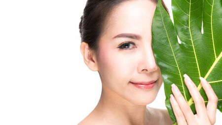 Foto für Close-up studio shot, Beautiful young woman with clean fresh skin holding green leaves. Proposing a product. Gestures for advertisement isolated on white background. - Lizenzfreies Bild