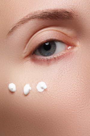 Photo pour Close-up of beautiful woman eye. Woman applying moisturizing cream - image libre de droit