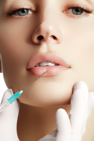 Photo pour Portrait of young  woman getting cosmetic injection. Closeup of beautiful woman gets injection in her face. Filler injections.  Lip augmentation. Beautiful perfect lips - image libre de droit