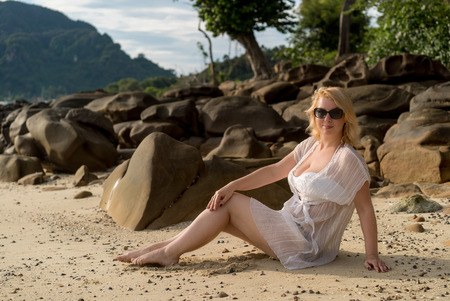 Young blonde woman on a beach in beach dress