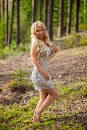 Photo pour Young beautiful blonde woman in gray sexy transparent dress - neglegee pegnoir underwear posing in forest in summer - image libre de droit
